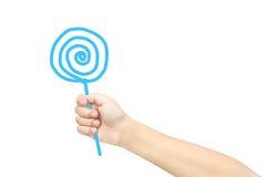 La mano del niño se imagina el caramelo del control Fotos de archivo