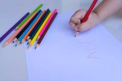 La mano del ni?o que se prepara para escribir en una hoja de papel blanca con los l?pices coloreados Educaci?n y concepto de las  fotos de archivo