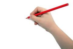 La mano del niño drena un lápiz rojo Imagen de archivo