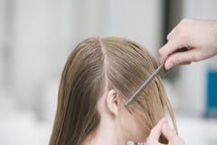 La mano del parrucchiere che pettina i capelli del cliente prima del taglio di capelli in salone fotografia stock libera da diritti