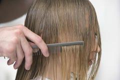 La mano del parrucchiere che pettina i capelli del cliente in salone fotografia stock libera da diritti