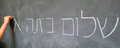La mano del pequeño niño escribe hola saludos del primer grado en hebreo Imagen de archivo