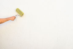 La mano del pittore sta dipingendo una parete della casa con il rullo fotografie stock