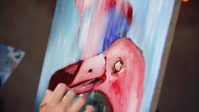 La mano del pittore sta disegnando i dettagli su un'immagine con gli uccelli rosa video d archivio