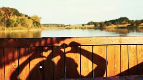 La mano del plexo dibuja un corazón una sombra del sol almacen de video
