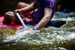 La mano del primer de hombres jovenes está transportando en balsa en el río Fotografía de archivo