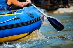 La mano del primer de la persona joven está transportando en balsa en el río Fotos de archivo