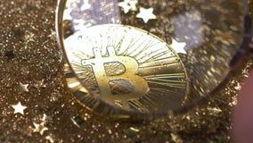 La mano del primer sostiene la lupa y muestra a Bitcoin el modelo real almacen de video