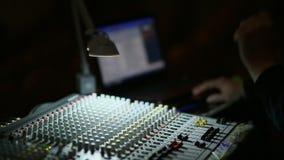 La mano del profesional que trabaja en mezclador audio en estudio almacen de metraje de vídeo