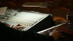 La mano del profesional que trabaja en mezclador audio en estudio metrajes