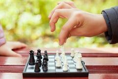 La mano del ragazzo tiene il pezzo degli scacchi sopra la scacchiera Immagine Stock