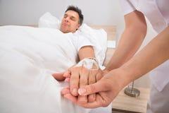La mano del ricoverato del gocciolamento del dispositivo di venipunzione Immagini Stock