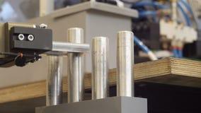 La mano del robot pone la columna del metal en la tabla
