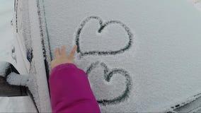 La mano del ` s del bambino disegna molti cuori sul vetro innevato dell'automobile un giorno di inverno stock footage