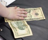 La mano del ` s del bambino tiene i dollari dei soldi su un fondo nero, il primo piano, dieci dollari di affari fotografie stock libere da diritti