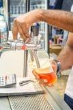 La mano del ` s del camarero sostiene un vidrio grande en el cual la cerveza ambarina fresca se vierta con espuma imagen de archivo libre de regalías