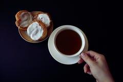 La mano del ` s de la mujer está sosteniendo una taza blanca de té imagenes de archivo