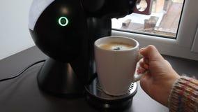 La mano del ` s de la mujer está tomando la taza de la mañana de café de la máquina del café almacen de video