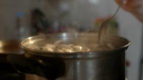 La mano del ` s de las mujeres está revolviendo la sopa con las setas metrajes