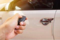 La mano del ` s de los hombres presiona en los sistemas de alarma para coches teledirigidos con Fotos de archivo