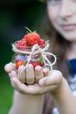 La mano del ` s de los niños sostiene fresas de cristal las pequeñas de un tarro Imagenes de archivo