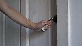 La mano del ` s de la muchacha abre la puerta de madera blanca almacen de metraje de vídeo