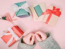 La mano del ` s de la muchacha de la belleza en paño gris del suéter prepara la caja de regalo para el soldado enrollado en el ej Foto de archivo