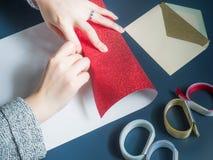 La mano del ` s de la muchacha de la belleza prepara la caja de regalo por el abrigo y embala el rojo presente Imagen de archivo