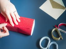 La mano del ` s de la muchacha prepara la caja de regalo por el abrigo y embala la actual caja FO del rojo Imagen de archivo