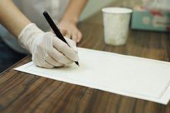 La mano del ` s de la muchacha sostiene una pluma en la hoja de papel foto de archivo libre de regalías