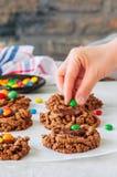 La mano del ` s de la mujer adornó las galletas de la jerarquía del ` s del pájaro del chocolate con el ganach Foto de archivo libre de regalías