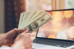 La mano del ` s de la mujer está llevando a cabo 100 dólares y gráficos de la demostración de la pantalla del ordenador portátil  Imagen de archivo libre de regalías