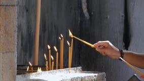 La mano del ` s de la mujer pone la vela ardiente metrajes
