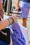 La mano del ` s de la mujer que lleva a cabo la muestra de la protesta en los profesores contra los armas se reúne con el hombre  fotografía de archivo