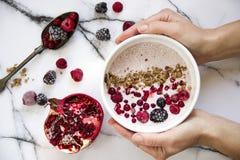 La mano del ` s de la mujer que sostiene un cuenco de yogur con los cereales y el bosque da fruto Granada en la tabla además Foto de archivo libre de regalías