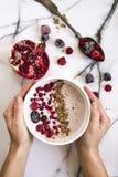 La mano del ` s de la mujer que sostiene un cuenco de yogur con los cereales y el bosque da fruto Granada en la tabla además Imagenes de archivo
