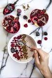 La mano del ` s de la mujer que sostiene una cuchara sobre un yogur con los cereales y el bosque da fruto Granada en la tabla ade Fotografía de archivo