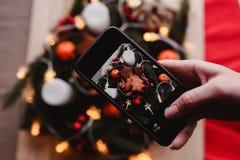 La mano del ` s de la mujer toma una foto móvil de la guirnalda del ` s del Año Nuevo con las galletas del pan de jengibre para e Fotografía de archivo