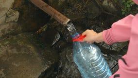 La mano del ` s de la mujer vierte el agua de manatial natural en la botella almacen de metraje de vídeo