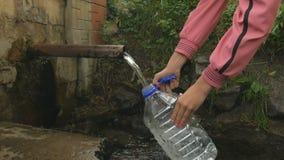 La mano del ` s de la mujer vierte el agua de manatial natural en la botella almacen de video