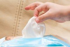 La mano del ` s dei bambini prende il tovagliolo bagnato Fotografia Stock