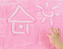 La mano del ` s del bambino estrae la casa ed il sole sulla sabbia Fotografie Stock