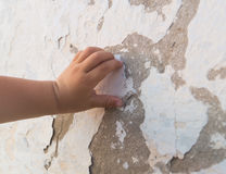 La mano del ` s del bebé toca la pared rota vieja del yeso Fotografía de archivo libre de regalías