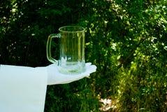 La mano del ` s del camarero en un guante del blanco sostiene un vidrio de cerveza contra la perspectiva de la naturaleza imagenes de archivo