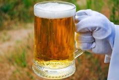 La mano del ` s del camarero en un guante del blanco sostiene un vidrio de cerveza contra la perspectiva de la naturaleza foto de archivo libre de regalías
