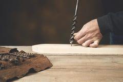 La mano del ` s del carpentiere è pronta a perforare il legno Immagine Stock