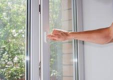 La mano del ` s del hombre abre una ventana Fotografía de archivo