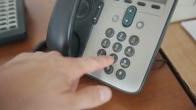 La mano del ` s del hombre está marcando un número de teléfono metrajes