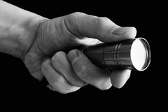 La mano del ` s del hombre que sostiene una linterna en fondo negro Imágenes de archivo libres de regalías