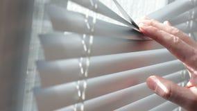 La mano del ` s del hombre separa las persianas para mirar hacia fuera la ventana almacen de video